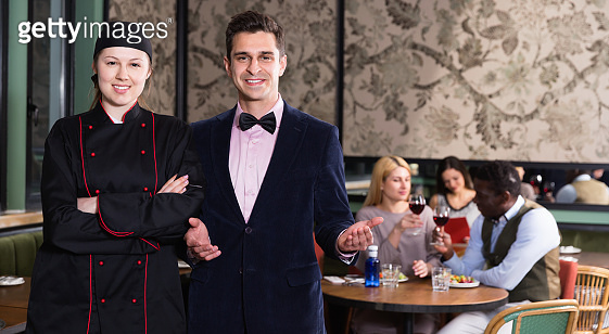 Confident female chef standing in restaurant hall with elegant  waiter welcoming guests