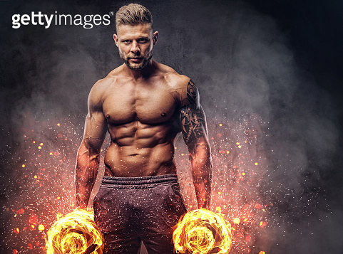 Handsome shirtless tattooed bodybuilder with stylish haircut and beard, wearing sports shorts, posing in a studio. Fire art concept.