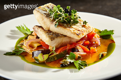 Pollock fish fillet with vegetables on white plate