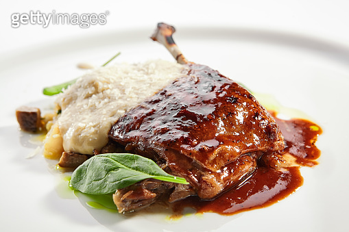 Duck leg with millet and hummus dish