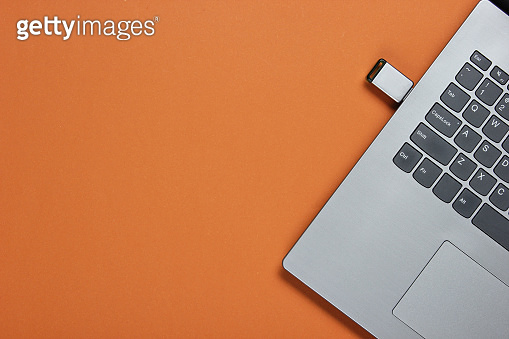 Laptop with flash drive on brown paper background. Studio shot, top view.