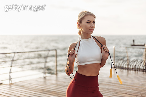 Portrait of a young sporting woman in sportswear with a skipping rope. Sportswoman posing on the beach at sunrise. Healthy lifestyle concept. Morning workout