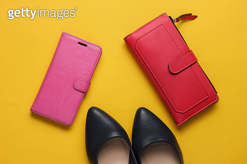 Studio fashion shot. High-heeled shoes, red wallet, smartphone in leather case on yellow background. Top view