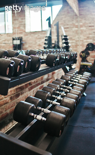 Set of black dumbbell with metal handles on a rack in the gym. Free weights training, bodybuilding