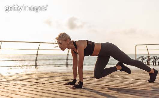 Healthy woman training on seaside promenade. Young sport woman in sportswear doing plank exercise on the beach at sunrise