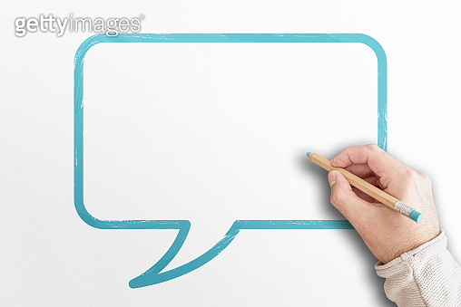 hand holding pencil writing in speech bubble with copy space