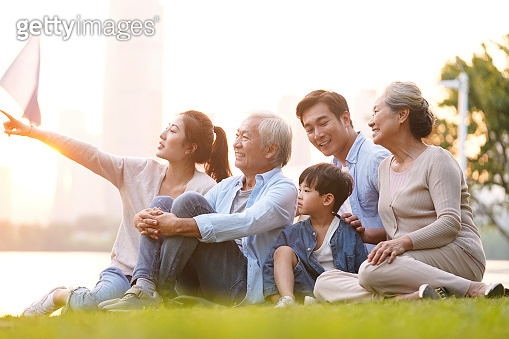 three generation asian family sitting on ground watching sunset