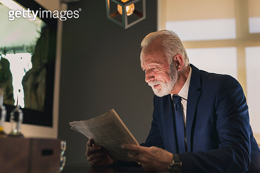 Senior businessman reading newspapers