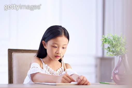 little asian girl sitting at desk writing or drawing