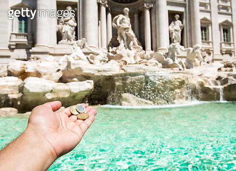 Girl is throwing coin at Trevi Fountain