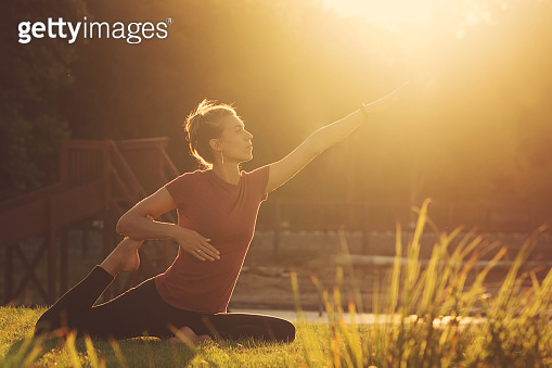 Girl doing yoga in the park at sunset
