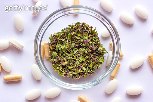 Dried herbs in a bowl on nutritional supplements pills background. Alternative herbal medicine, naturopathy and homeopathy, medical pharmaceutical drug, organic vitamins and multivitamins concept