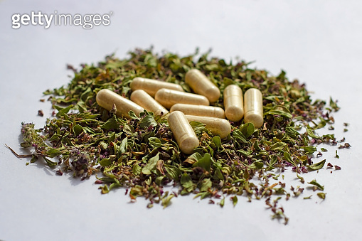 Nutritional supplements pills and capsules on dried herbs background. Alternative herbal medicine, naturopathy and homeopathy, medical pharmaceutical drug, organic vitamins and multivitamins concept