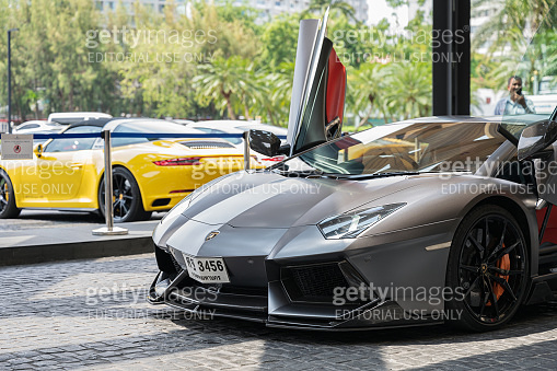 Opened vehicle door of Dark Lamborghini sport cars of famous brand parking on front of the Royal Cliff Beach Hotel