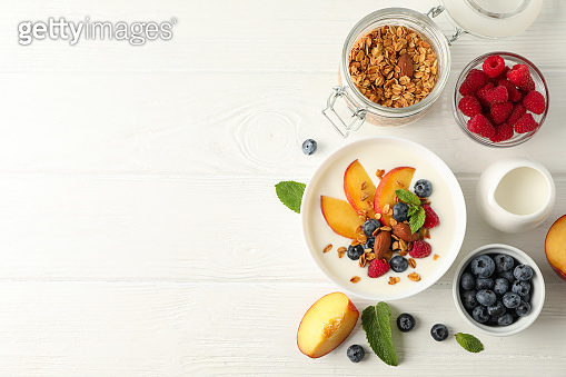 Flat lay composition with parfaits dessert and ingredients on white wooden background