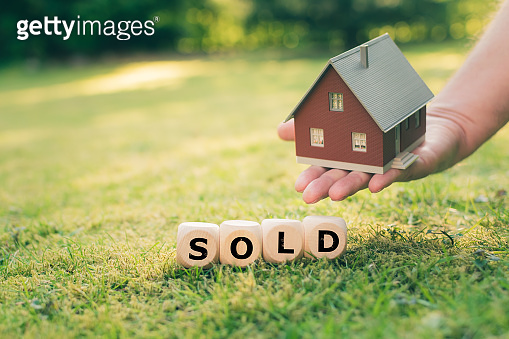 Concept of a sold house. A hand holds a model house above a meadow. Dice form the word