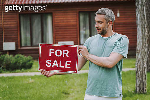 Handsome man holding for sale card outdoors