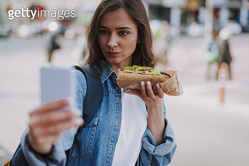 Pretty female making funny selfie with hot dog