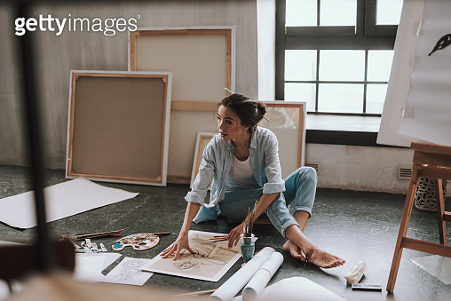 Barefooted lady looking away while sitting on the floor of art studio