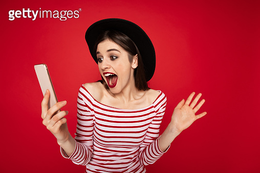Happy surprised girl looking at mobile phone
