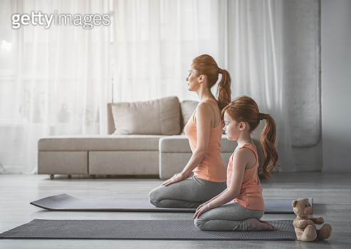 Woman and her child are meditating at home