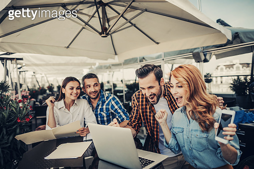 Young couple receiving good news online while smiling friends looking at them