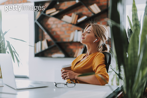 Calm woman relaxing in the office with coffee and music