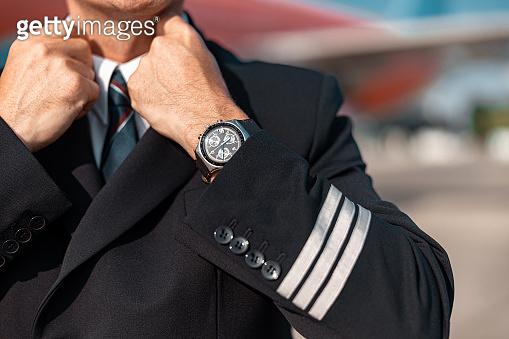 Close up of Caucasian pilot straightening his jacket before flight