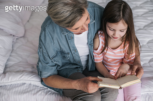 Gray-haired woman teaching her granddaughter to read book at home