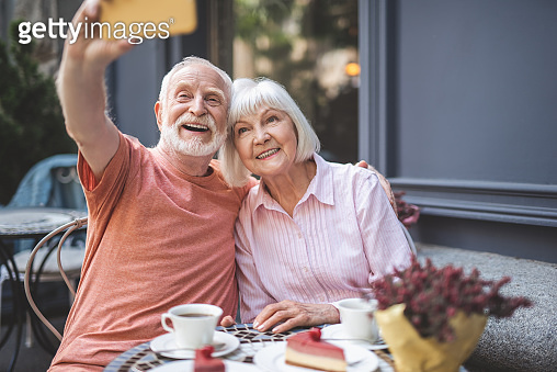 Happy senior couple making selfie in cafe