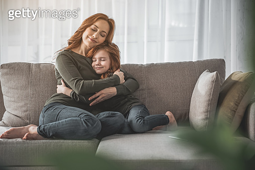 Mom and her little kid embracing with their eyes closed