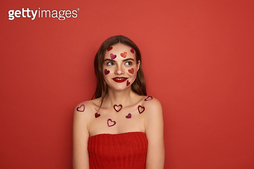Beautiful Caucasian woman is decorated with red heart-shaped stickers on color background