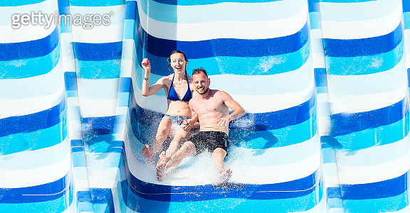 Young, attractive couple having fun, sliding at water park. swimming pool in luxury hotel