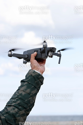 drone flying in air, catch by operator hand