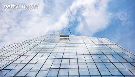 New York, Manhattan. Glass cleaning services, high building glass facade, view from below against blue sky background