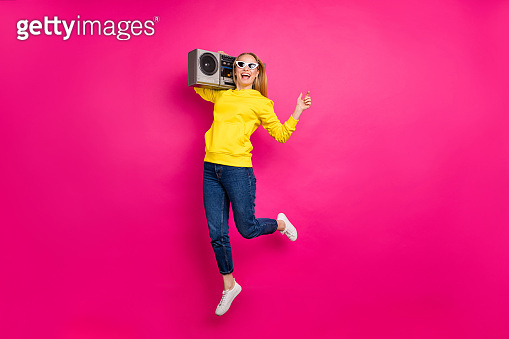 Photo of jumping high with vintage tape recorder on shoulders lady wear casual outfit isolated pink background