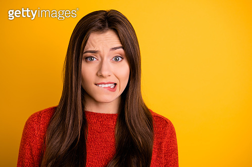 Portrait of disappointed scared girl bite her lips have trouble worry feel panic expression emotion wear red sweater isolated over yellow color background