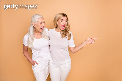 Portrait of astonished curly hairdo adults impressed discounts news notice ads decide advice tip choose recommend attention advertise suggest hug embrace isolated trendy outfit beige background