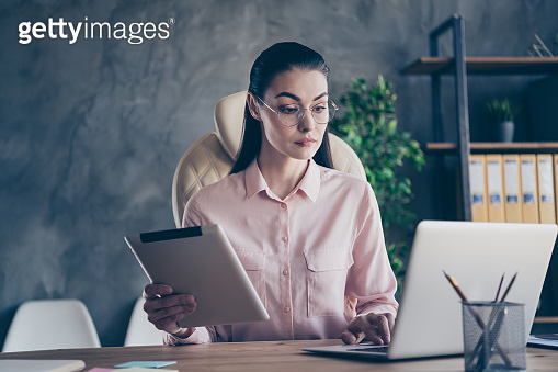 Photo of working serious concentrated business woman holding tablet with her hands analyzing two sources of information looking into screen intently