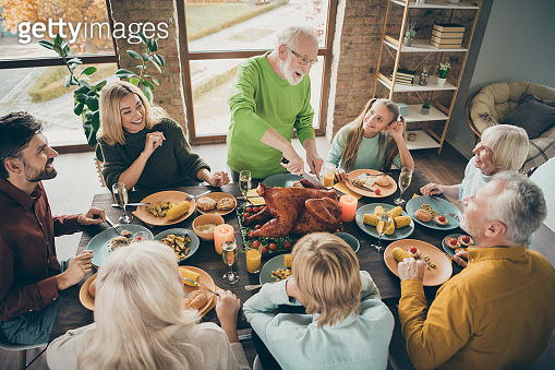 Photo of big family sit feast meals table around blessing roasted turkey eldest grandfather making slices hungry relatives waiting excited in living room indoors