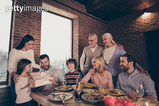Close up photo people big family company brother sister granny mom grandpa son daughter give large giftbox box package daddy dad father sit festive holiday tasty dishes table loft house indoors