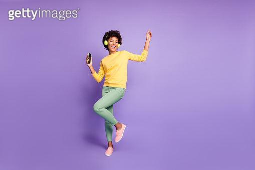 Full length body size photo of trendy stylish cute free girlfriend wearing green pants trousers yellow sweater footwear in headphones listening to music dancing isolated violet pastel color background