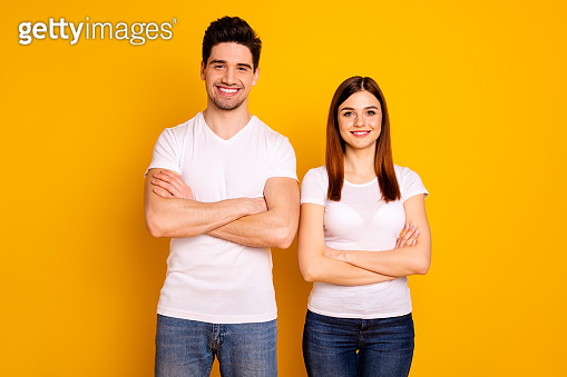Close up photo beautiful cheer she her he him his pair stand side teamwork self-confident professionals specialists work job reliable workers wear casual white t-shirts isolated yellow background