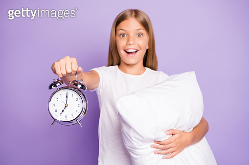 Portrait of excited positive blonde hair kid awake in morning look at time clock hold hand people amazed scream omg want hurry to school wear white t-shirt isolated violet purple color background