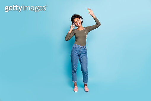Full length photo of cheerful positive dark skin hipster girl listen music use headset sing her favorite stereo melody song raise hands wear green pullover denim jeans isolated blue color background