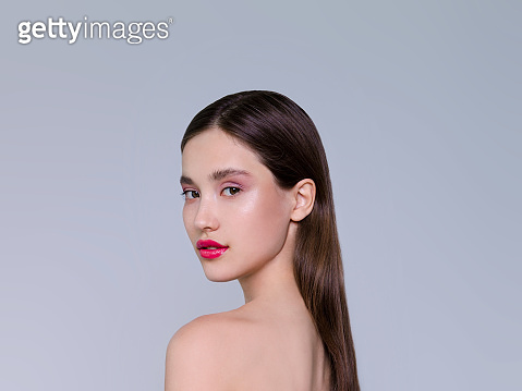 Beautiful brunette young woman with glowing make-up on gray background Fashion model close up shot