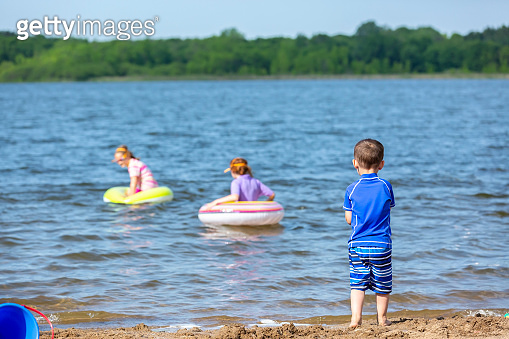 Young Boy At Beach Watching Sisters In the Water