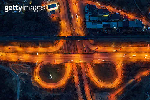 Aerial view of transport junction, city roads, top view from drone, car traffic at night