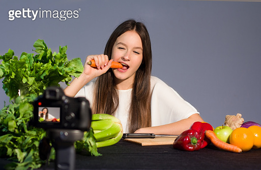 Teenage blogger talks to followers about the advantages of eating organic fruit and vegetables. Concept of communication to adolescents by a young influenzer of the benefits on well-being due to healthy lifestyle and healthy food