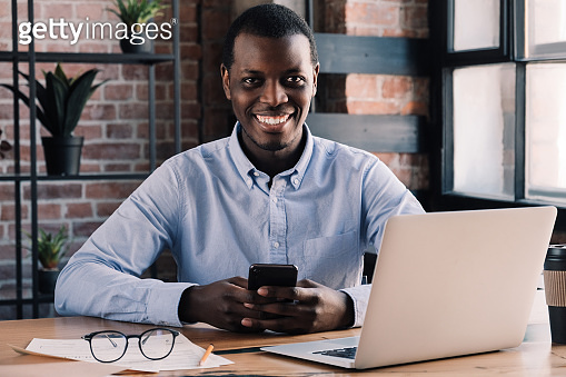 African guy working in cafe holding smartphone in hands and looking at camera with smile